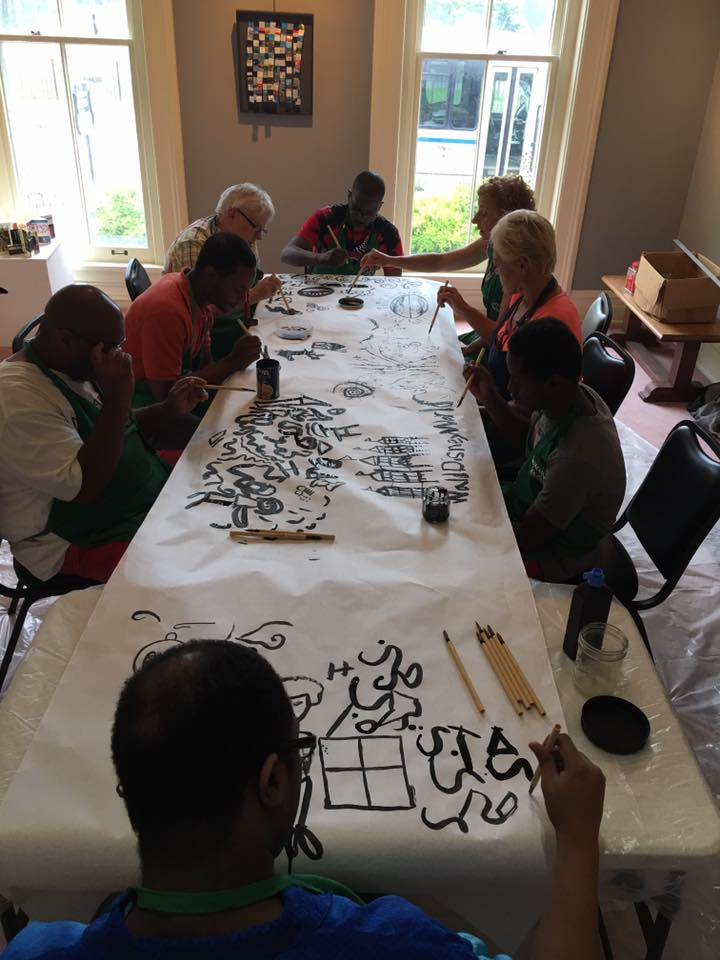 Artists working on community-based art project panels